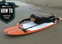 Paddling prone on a SUP